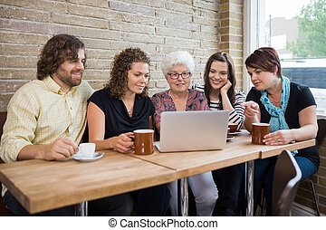 Woman With Friends Using Laptop At Coffee shop - Senior...