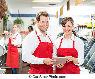 Butchers With Digital Tablet Standing In Store