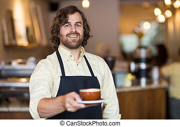 Confident Waiter Holding Coffee Cup In Cafe