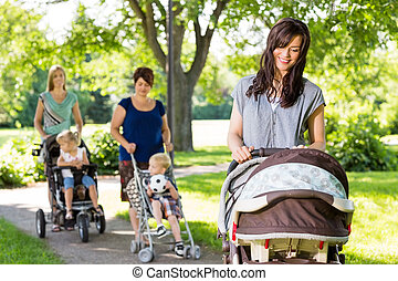 Mother Looking At Baby In Stroller At Park - Young mother...