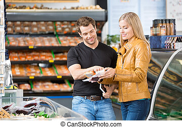 Couple, Checking, Product, Ingredients, At, Butcher's, Shop