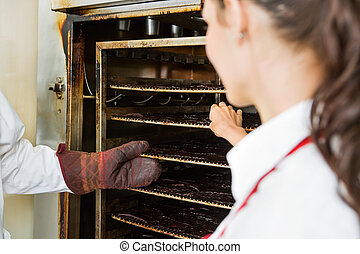 Workers Removing Dried Meat Slices From Oven At Shop - Male...
