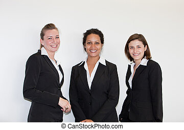 Three attracttive multiethnic young businesswomen in black business suits