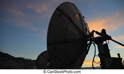 Catching up a frequency - A satellite antenna at sunset,...