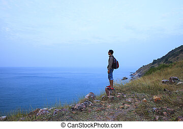backpack man standing on rock mountain and looking to ocean...