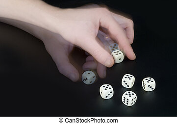 Cheating - A man cheating whilst playing dice, turning a...