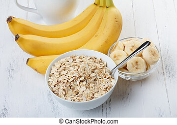 Bowl of oat flakes with sliced banana close-up on wooden...