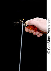 Hand lighting a magnesium sparkle stick - A male hand,...