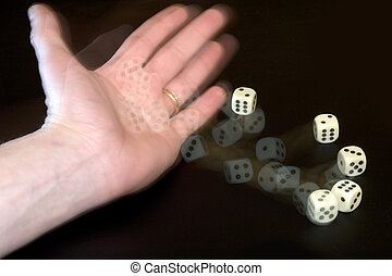 Throwing Dice - A male hand with a wedding ring throwing...