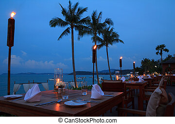 Outdoor restaurant tables, dinner setting on the beach at...