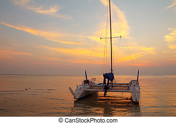 Catamaran on tropical beach at sunset