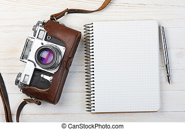 Blank notebook with fountain pen and retro camera on wooden...