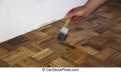 Shiny as a varnished parquet - A man varnishing a parquet