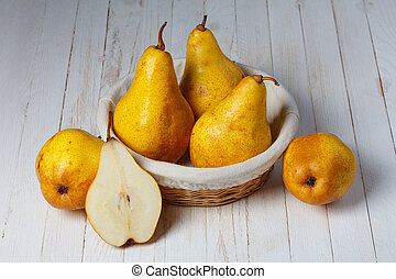 Juicy pears in a basket on wooden table