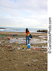 Beach full of dirt and dump with young woman trying to clean...