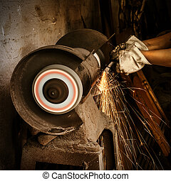 Abrasive cutting - Worker cutting metal with grinder. Sparks...