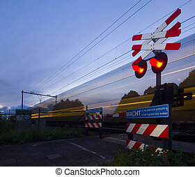 Passing train - A train passing a rail crossing, surrounded...