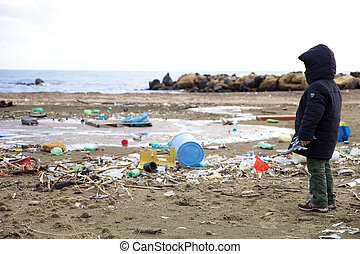 Kid watching pollution on the beach ecological disaster -...