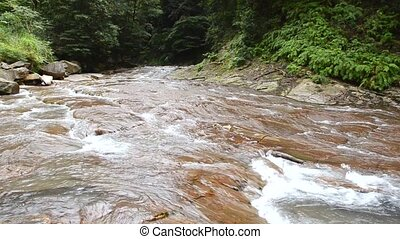River flowing over the reddish brown rock mass with lot of...
