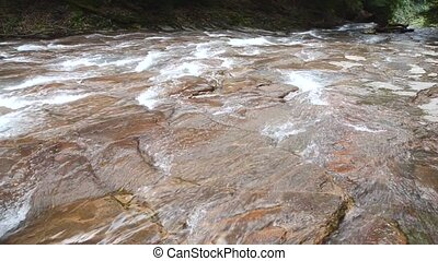 River flowing - River going down the reddish brown rock mass...