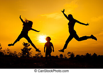 Happy  family jumping on the  road in the  sunset time.
