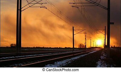 Railroad track with train at sunset