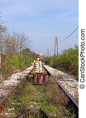 little girl with suitcase and umbrella standing on railroad