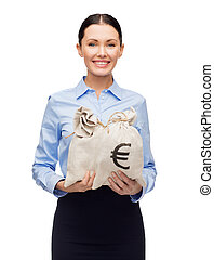 businesswoman holding money bags with euro - business and...