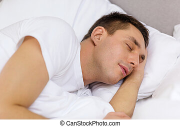 handsome man sleeping in bed - hotel, travel and happiness...