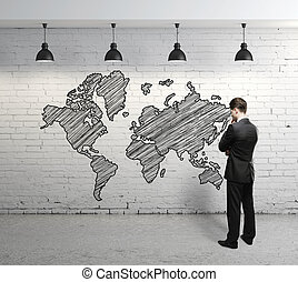 man looking map - man looking at world map on brick wall