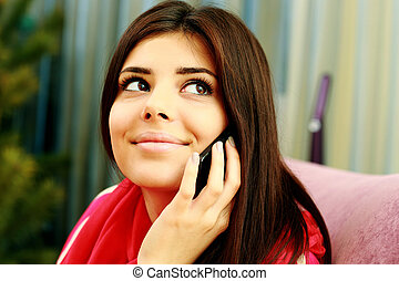 Closeup portrait of a young smiling woman talking on the phone and looking up