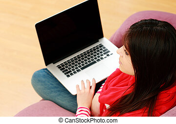 Young beautiful woman sitting on the sofa with laptop at...