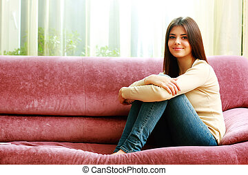 Young happy smiling woman sitting on the sofa at home
