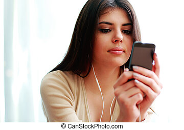 Young beautiful woman using smartphone and listening the...