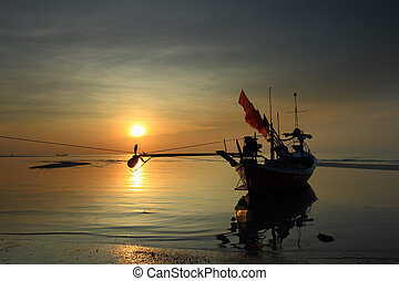 Stunning golden sunset over sea and sky with fishing boat...