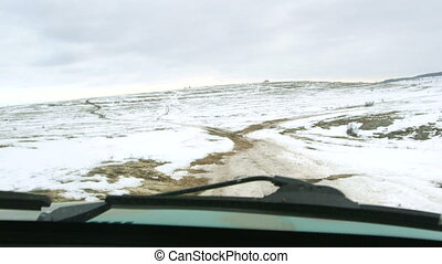 Off-road vehicle riding through the snowy Crimean plateau at...