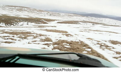 Off-road car riding through the snowy mountain plateau