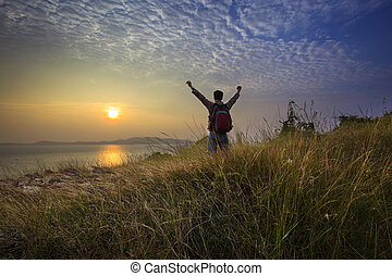 young man standing and rising hand as victory on grass hill...