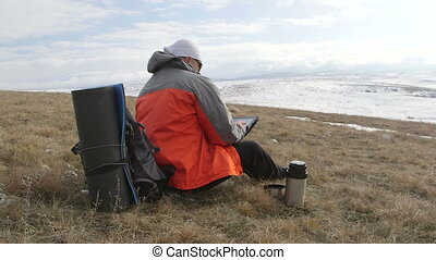 Hiker using tablet computer on the snowy mountain plateau