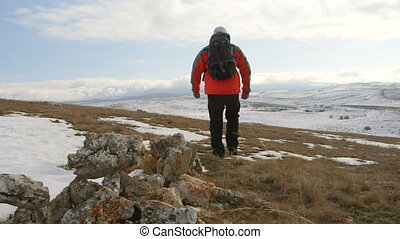 Man hiker walking through the snowy mountain plateau