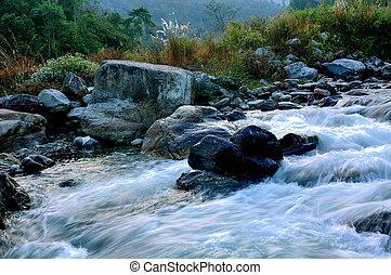 River water flowing through rocks at dawn - Reshi River...