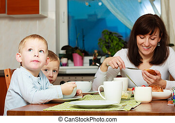 Family eating breakfast at table - Family eating corn flakes...