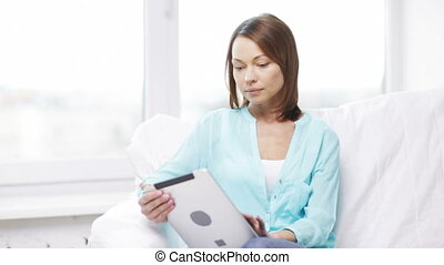 calm woman with tablet pc computer at home - home,...