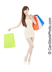full length of smiling asian woman with shopping bags