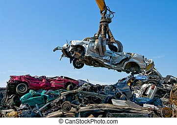 Junkyard picking up car - Crane picking up a car in a...