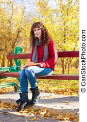 Girl reading a book in autumn park