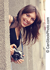 smiling woman with camera outdoors