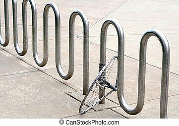 abandoned bike wheel locked with bike rack