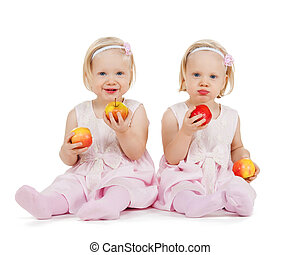 two identical twin girls playing with apples - children,...