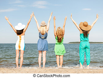 girls with hands up on the beach - summer holidays and...